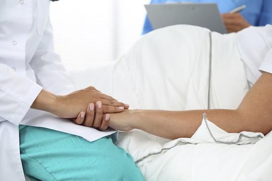 hamile kadının elini tutan doktor